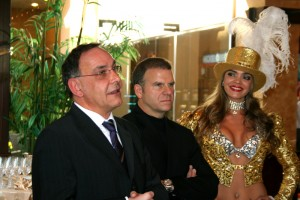 Thomas Geissler, left, CEO of Gold to go's parent company Ex Oriente, talks Wednesday about the newest attraction at the Golden Nugget, an ATM that dispenses gold. Tilman Fertitta, middle, CEO of Landry's which owns the Golden Nugget, and a showgirl look on.
