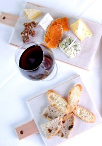 The cheese presentation shown with fresh bread and wine at Morels French Steakhouse & Bistro.