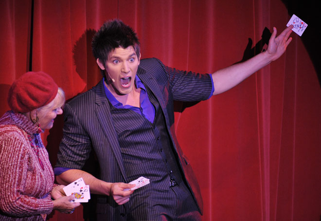 Vegas Magic Theater host Ben Stone gets the help of a volunteer for a card trick on stage.
