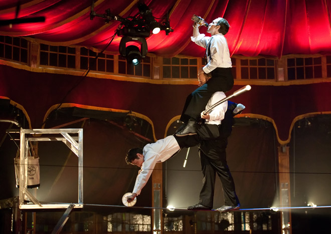 The Esteemed Gentlemen of the highwire balance above the crowd while taking shots of whiskey. Photo by Tom Donoghue