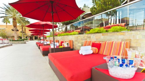 Daybeds and umbrellas line the perimeter of Palms Pool
