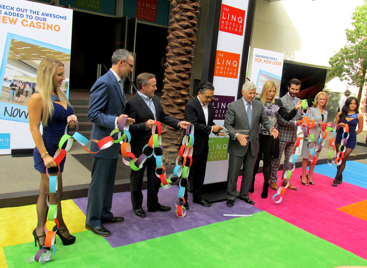 Caesars Entertainment executives cut a chain made of multicolored construction paper rings.