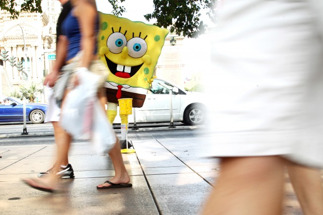 A man wearing a SpongeBob outfit waits in the shade to have his photo taken for tips on the Strip Saturday, June 29, 2013.