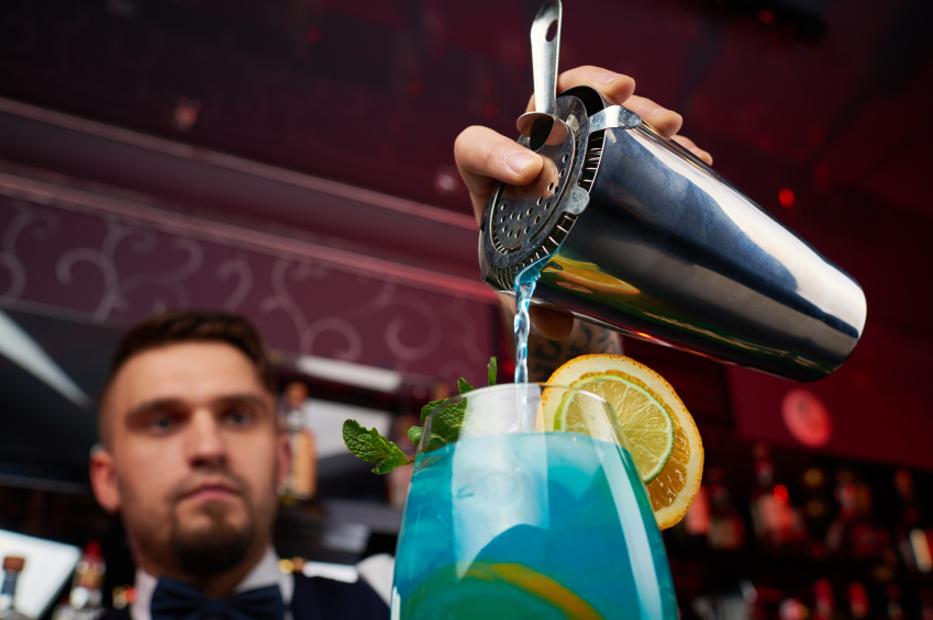 Bartender pouring blue cocktail into glass decorated with orange and lime slices