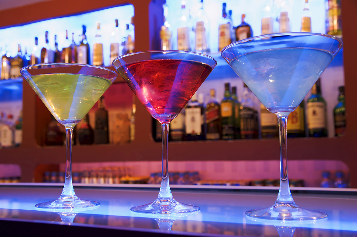 blue, red and yellow cocktail drinks on a bar